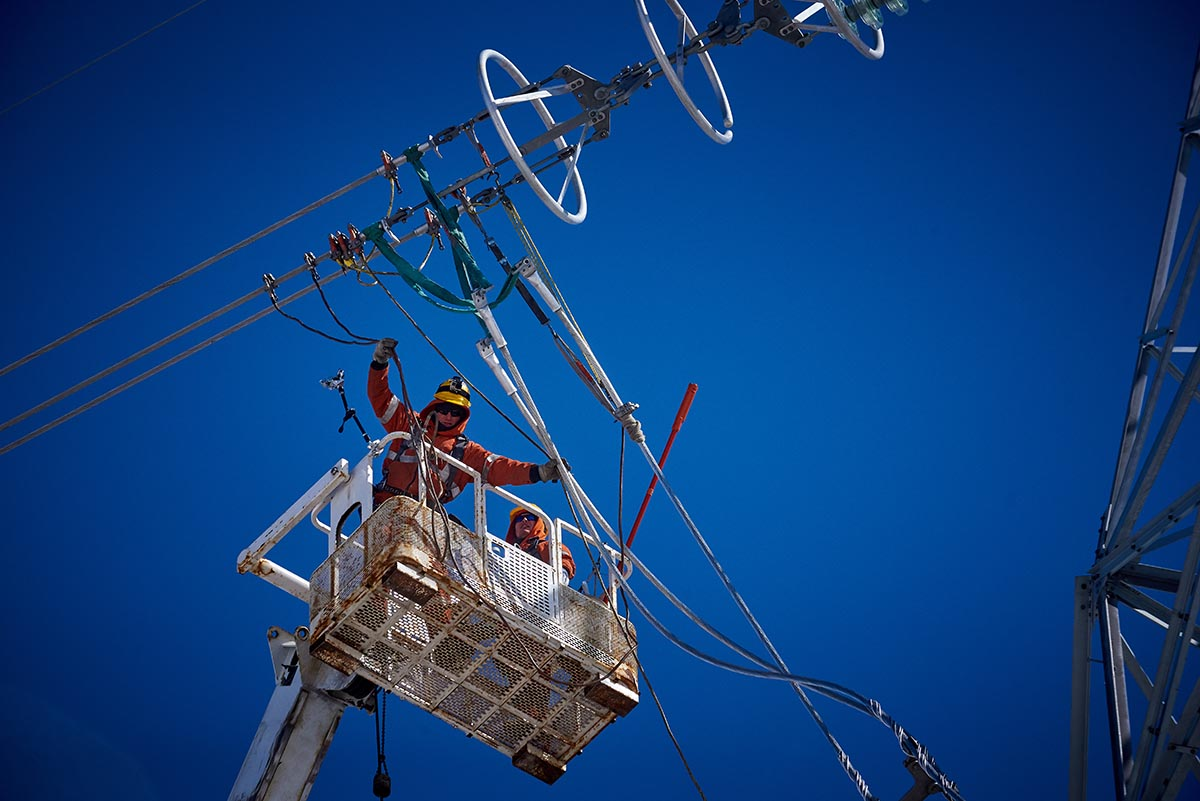 Photo of power line technicians working on a Bipole tower.