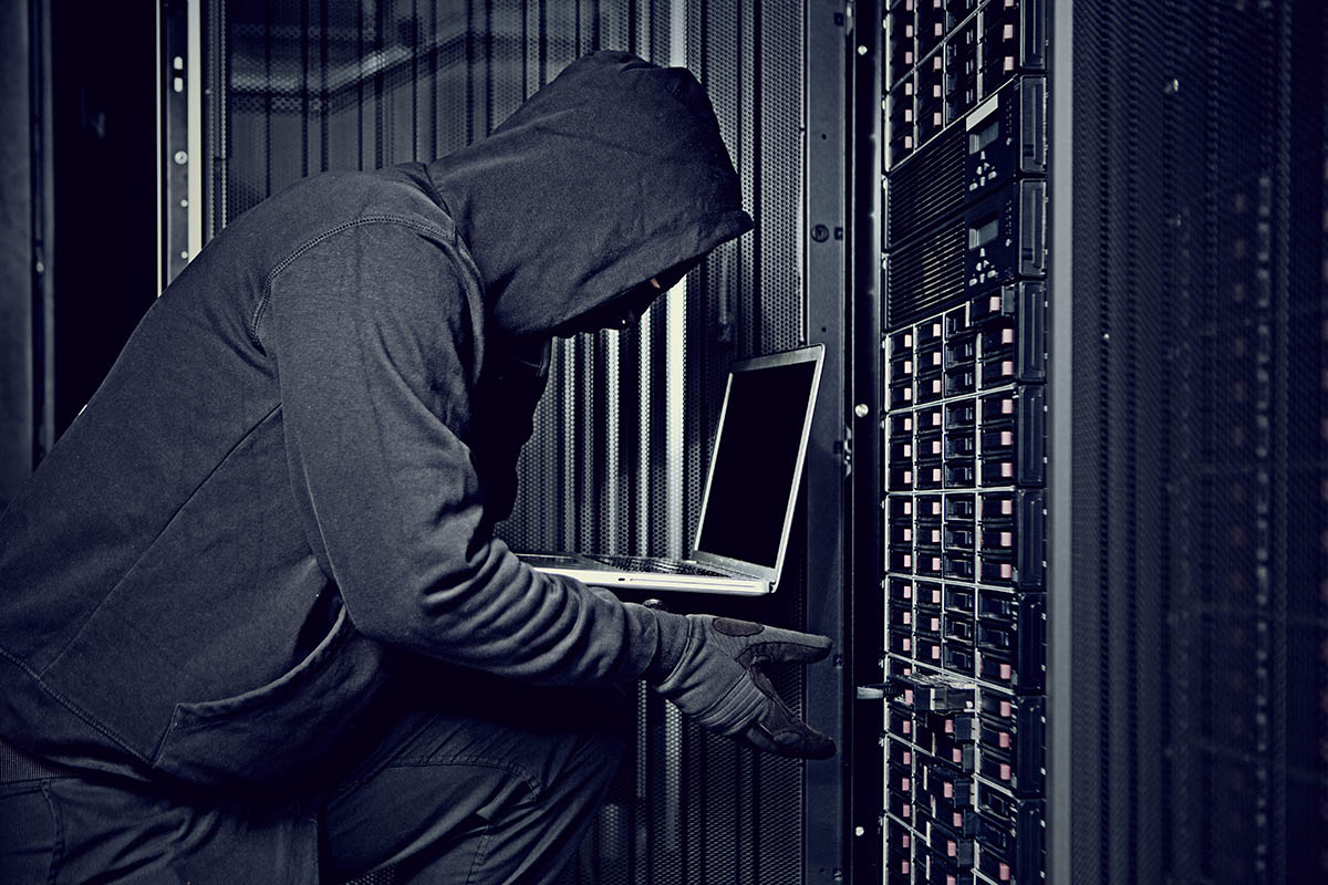 Photo of hacker using a laptop in a server room.